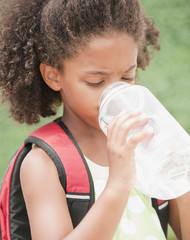 Mixed race girl drinking water