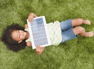 Mixed race girl laying with solar panel