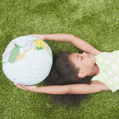 Mixed race girl holding globe