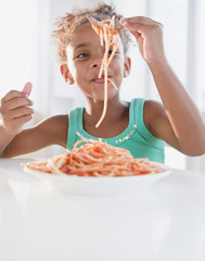 Mixed race girl eating spaghetti