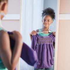 Mixed race girl looking at shirt