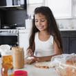 Hispanic girl making peanut butter sandwich