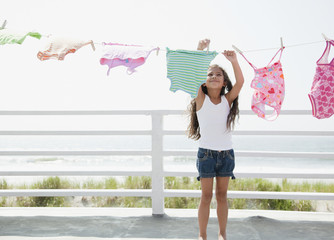 Hispanic girl hanging laundry to dry