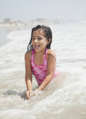 Hispanic girl playing in ocean