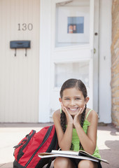 Hispanic girl sitting with school books on front stoop
