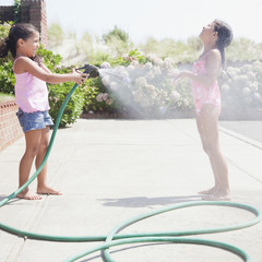 Hispanic girl spraying sister with hose