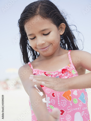 Hispanic girl applying sunscreen lotion