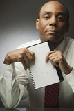 African businessman holding datebook