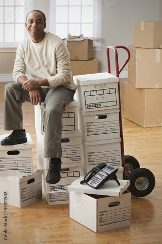 African man sitting on moving boxes