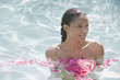 Nude mixed race woman in swimming pool with rose petals