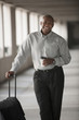 African businessman standing in parking garage with luggage