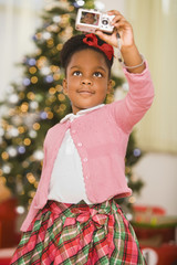 African girl taking self-portrait at Christmas
