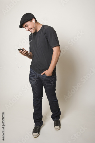 Hispanic teenager listening to mp3 player