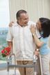 Hispanic woman encouraging husband using walker