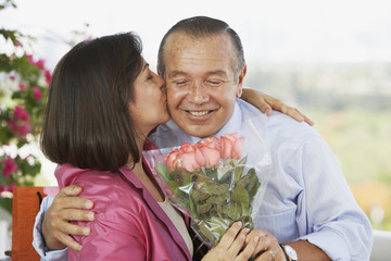 Hispanic man giving wife flowers