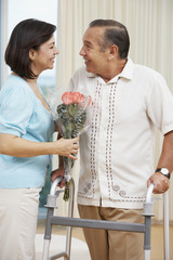 Hispanic woman bringing husband flowers