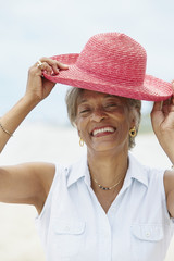 African woman putting on straw hat