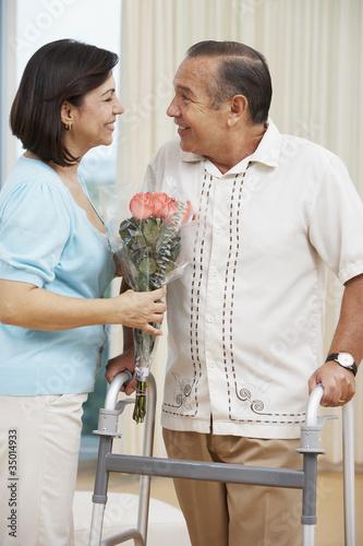 Hispanic woman bringing husband flowers