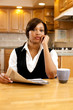 Serious African woman with paperwork and coffee in kitchen