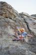 Mixed race girl rock climbing