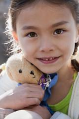 Mixed race girl holding teddy bear