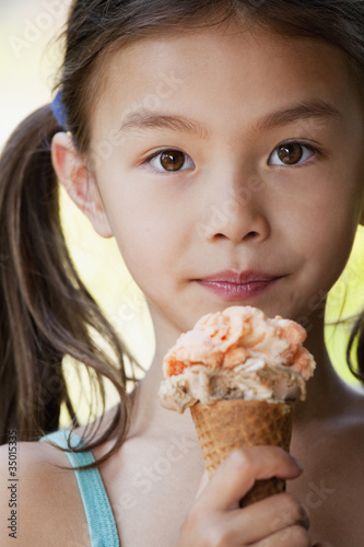 Mixed race girl eating ice cream cone