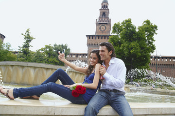 Couple taking self-portrait near fountain
