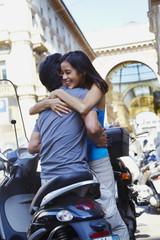 Man on scooter hugging girlfriend