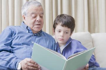 Hispanic grandfather reading book to grandson