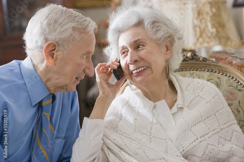 Senior Hispanic couple using cell phone