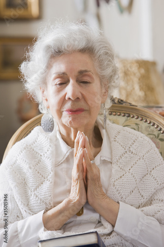 Senior Hispanic woman praying
