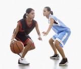 Mixed race women playing basketball