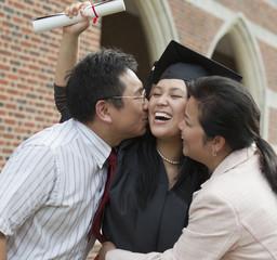 Chinese parents kissing graduate daughter
