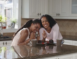 African American sisters in kitchen eating cake