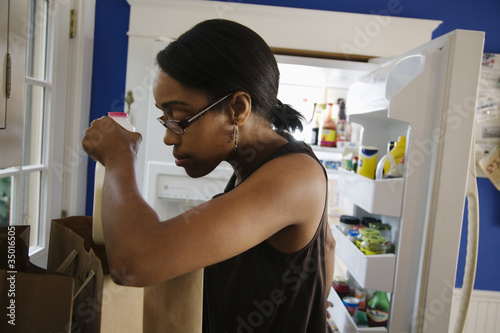 African woman unloading groceries in kitchen
