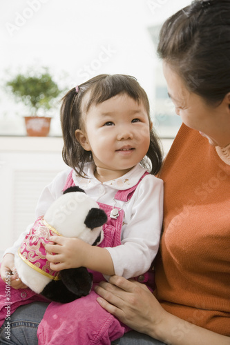 Chinese mother holding daughter on lap