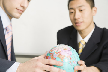 Businessmen looking at small globe