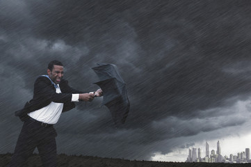 Mixed race businessman struggling with umbrella in storm