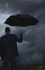 Black businessman holding umbrella in storm