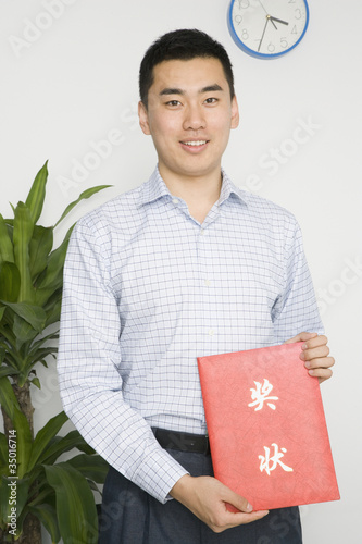 Chinese man holding paper with Chinese symbols