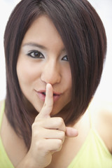 Hispanic teenage girl making shhh gesture