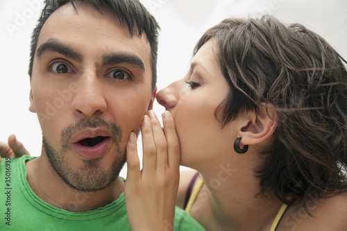 Hispanic woman whispering to boyfriend