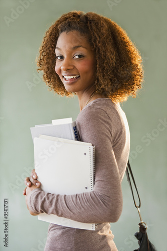 Mixed race woman holding books