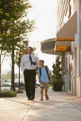 Caucasian businessman and son walking on city sidewalk