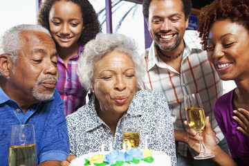 Family watching African American woman blowing out birthday candles