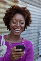 African American woman text messaging with cell phone