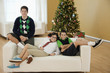 Mixed race family sitting on couch at Christmas