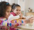 Hispanic sisters eating spaghetti