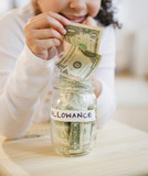 Hispanic girl putting allowance into jar
