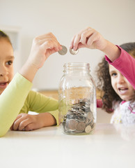 Hispanic sisters putting coins in jar